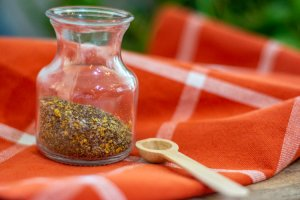 lemon pepper seasoning in a decorative jar with a wooden teaspoon on an orange cloth