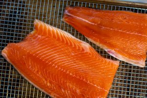 Salmon fillets on a cooling rack to dry and form a pellicle