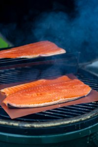 salmon fillet on a copper grilling mat on the big green egg with smoke billowing out