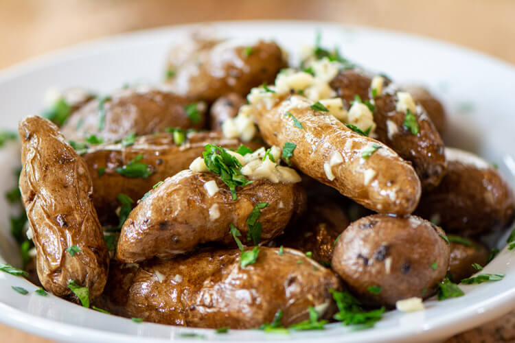 bowl of smoked potatoes with a delicious garlic and butter topping