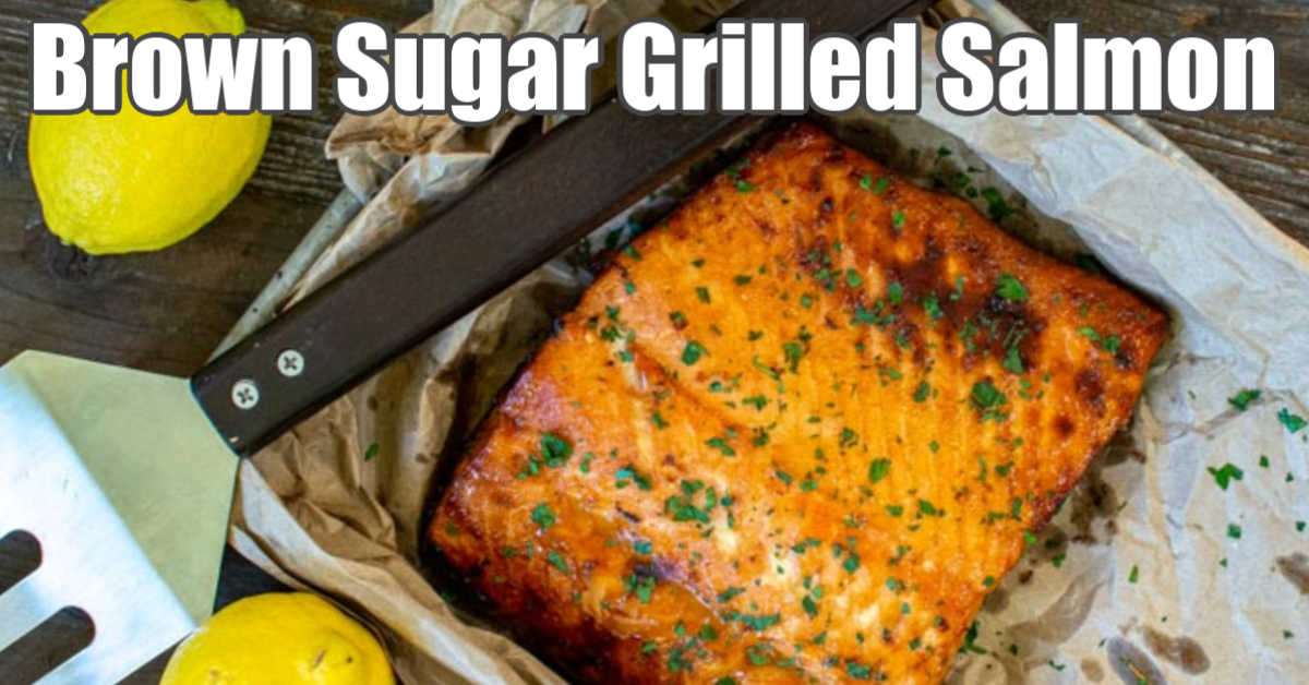 grilled brown sugar salmon on a lined sheet pan with grilling tools and fresh lemons