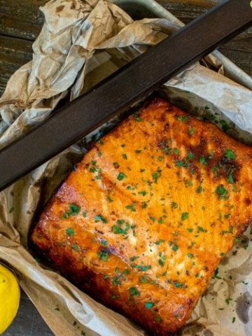 Delicious grilled brown sugar salmon fillet on a small sheet pan with grilling tools and fresh lemons