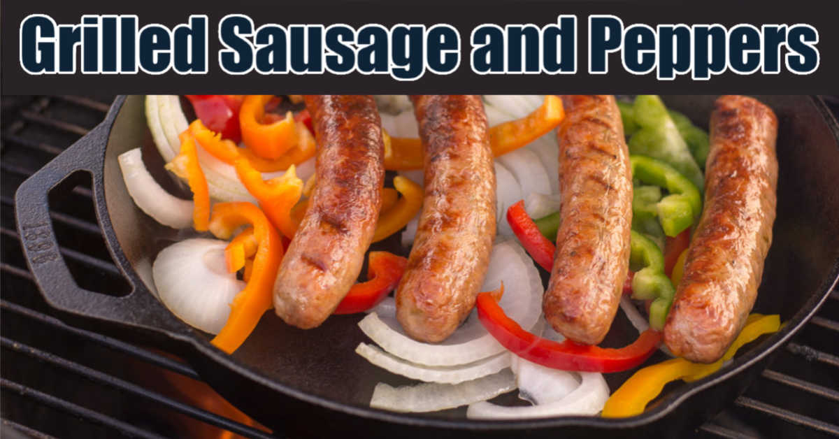 grilled sausage on top of onions and colorful pepper slices in a cast iron skillet on the grill