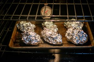 baking potatoes in the oven wrapped in foil and placed on a baking sheet