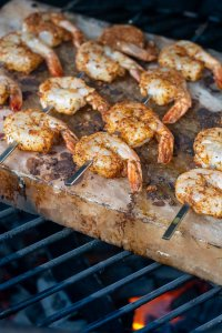 heated salt block on the big green egg with skewers of shrimp with a fanatic seasoning