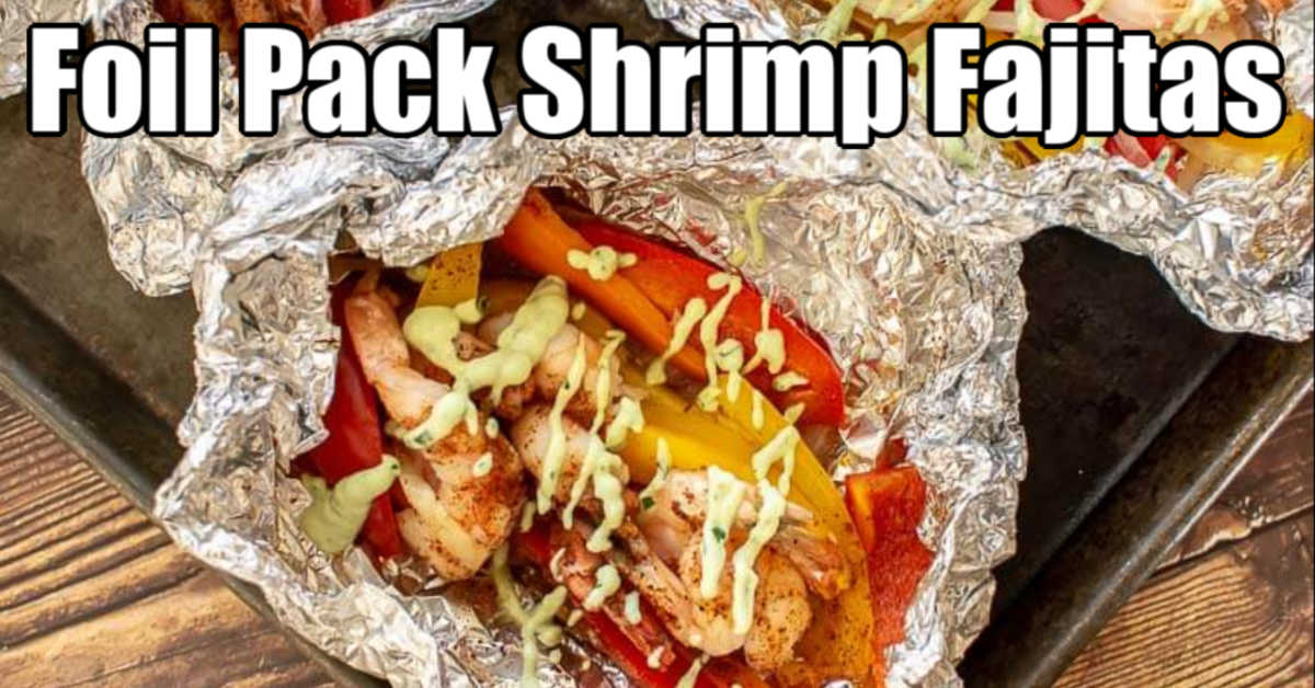 shrimp fajitas in an aluminum foil pack with avocado dressing drizzled on top