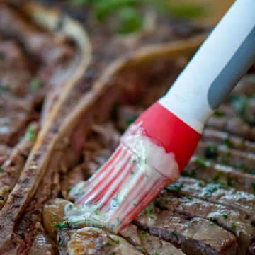 brushing on the garlic and herb butter on the sliced steak