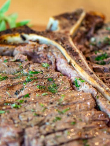 steak sliced with the bone in and brushed with herb butter
