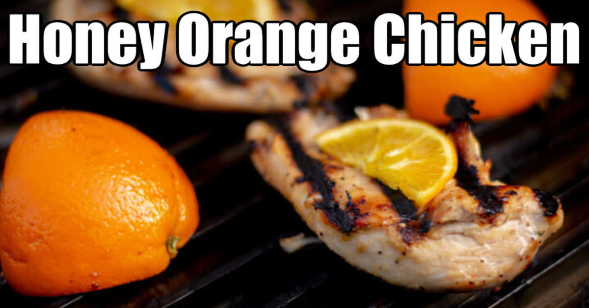 grilled chicken breast on the GrillGrate next to a quarter orange