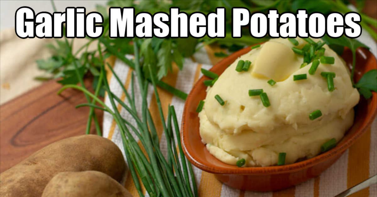 mashed potatoes in a small side dish with a pad of butter and chopped chives