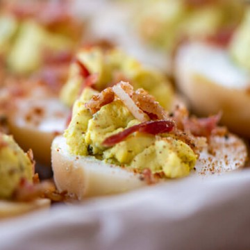 bacon topped deviled eggs on a tray and sprinkled with additional seasoning