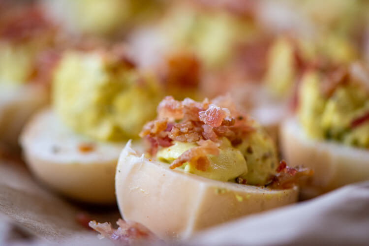 closeup of the tray of deviled eggs and topped with crumbled bacon