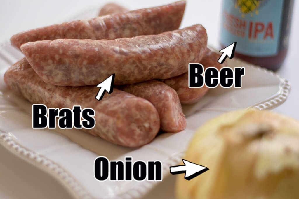 three ingredients for the beer brats. Brats stacked on a plate, a whole onion and a bottle of beer.