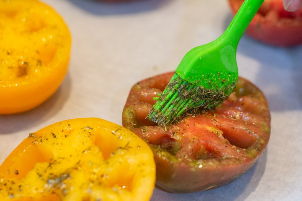 brushing the herb and olive oil mixture on the tomato that was cut in half