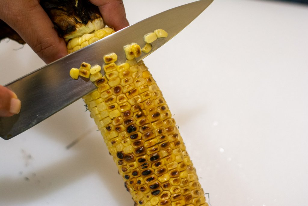 slicing the kernels off of the ear of corn for the black bean salsa