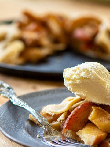 slice of apple crostata on a plate with ice cream and the rest of the dessert in the background