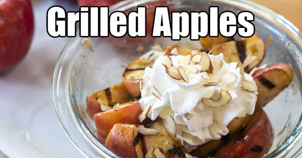 bowl of grilled apples topped with whipped cream and almond slivers