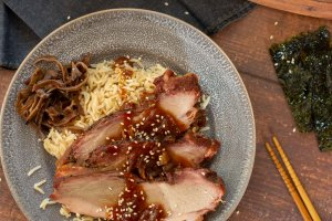 basmati rice, rehydrated mushroom slices and chopsticks with a plate of pork