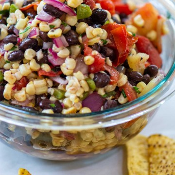 bowl of black bean and corn salsa with chips in the foreground