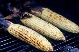 roasted corn on the grill with the husks pulled back
