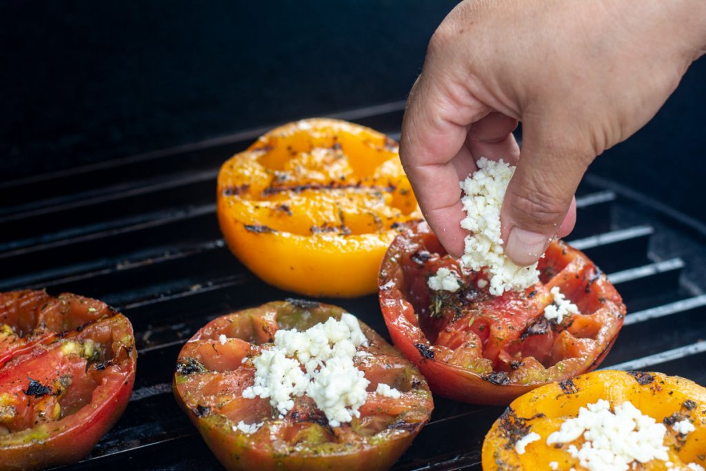 sprinkling freshly grated mozzarella cheese in the tomato halves
