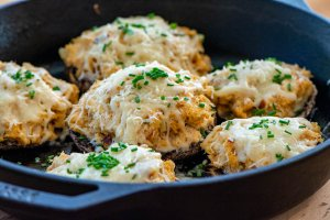 grilled stuffed portobello mushrooms in a cast iron skillet filled with smoked salmon and topped with parmesan cheese