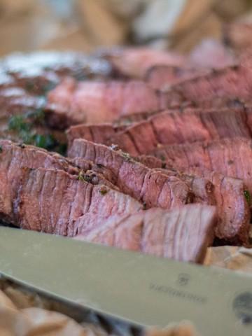 sliced bison on butcher paper with a sharp knife
