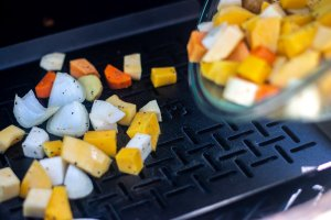 pouring the root vegetables on the cast iron pan on the grill