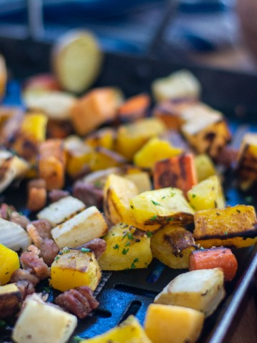 cast iron pan on the table with roasted vegetables and the cooked pork belly mixed in