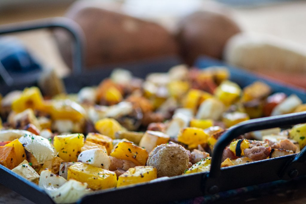 Front view of the roasted vegetables on the cast iron pan with whole root vegetables in the background.