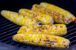 Ears of corn on the grating with a dark char from the direct heat of the grill