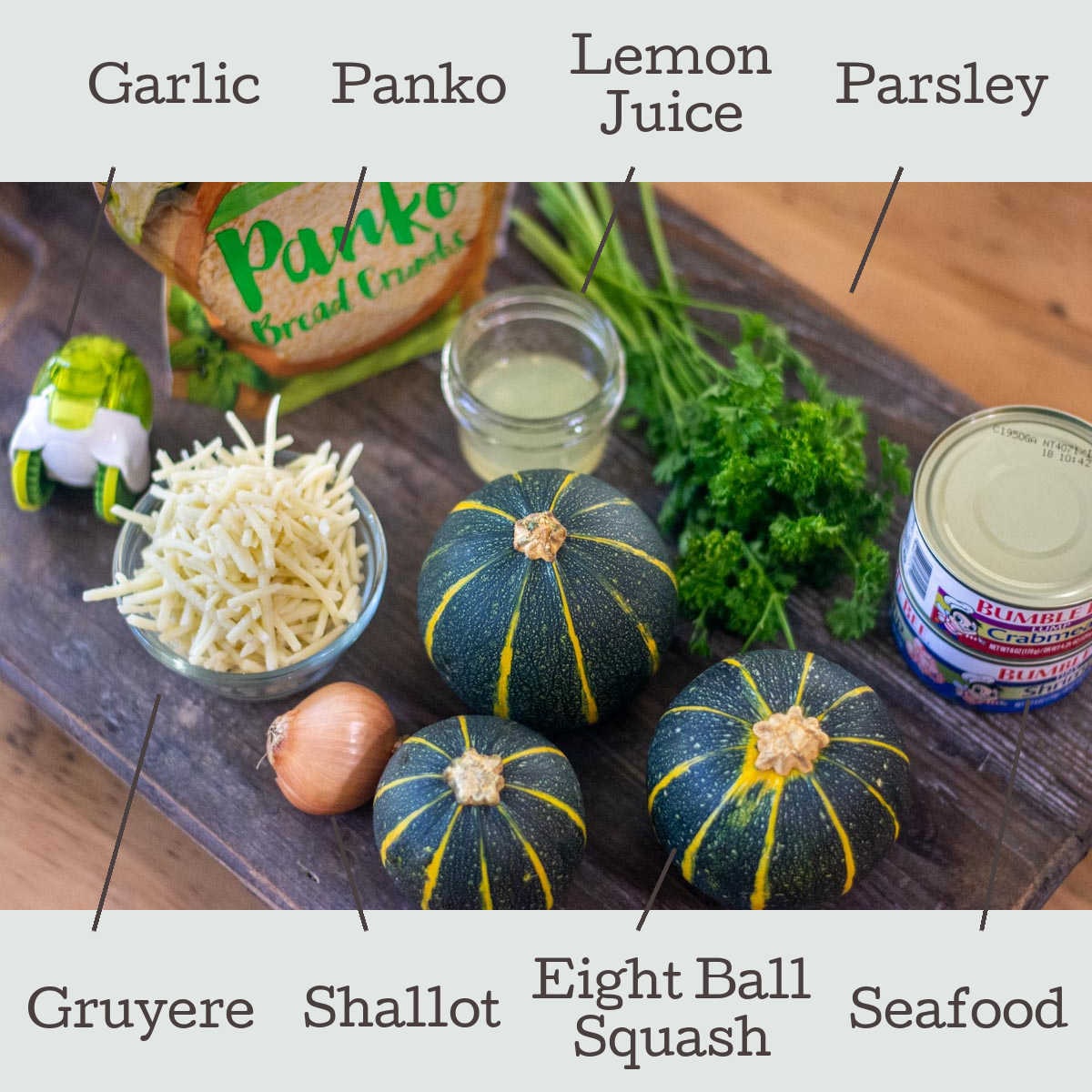 ingredients for the seafood stuffed squash on cutting board with labels.