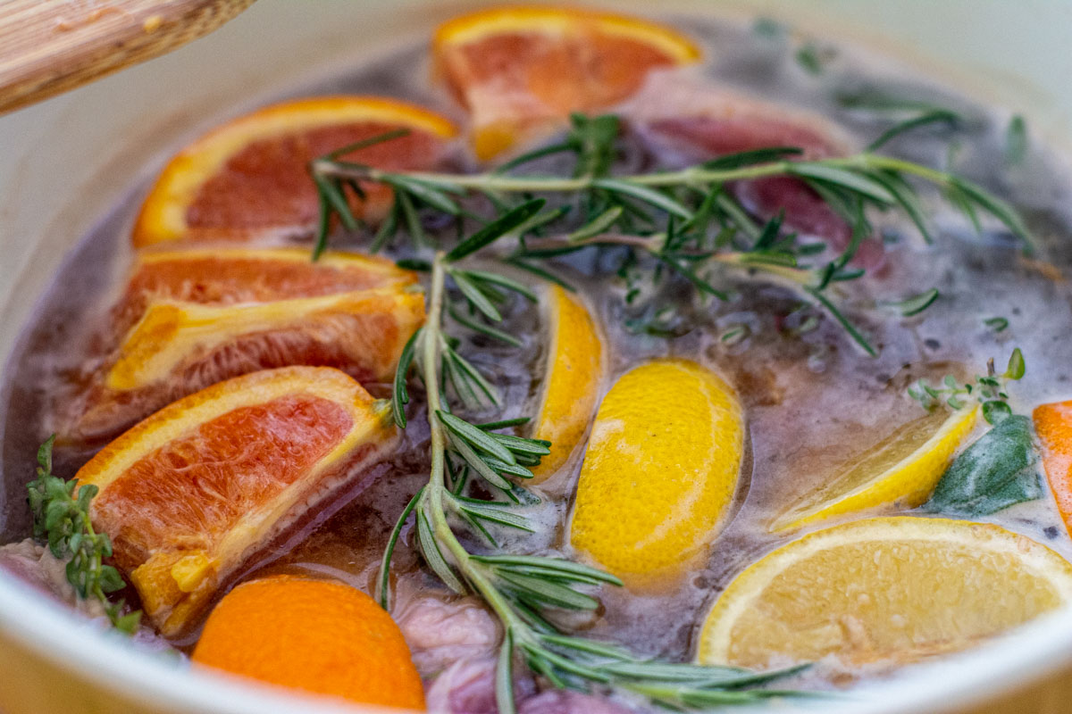 turkey in a bowl filled with beer, salt, brown sugar, lemons, oranges and herbs for a wonderful brine