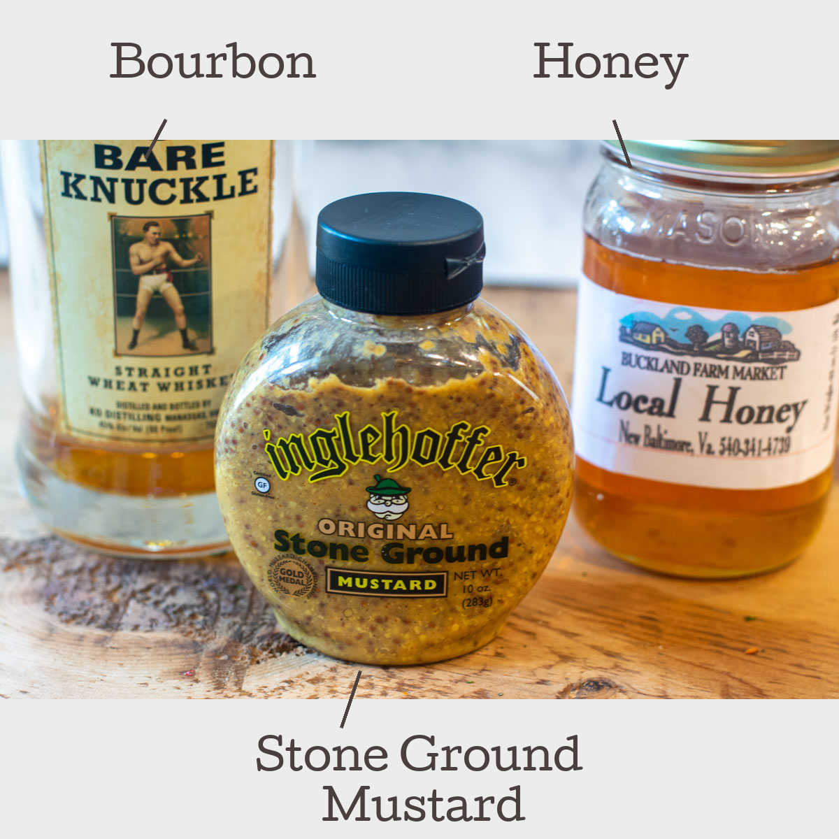 three ingredients on a table for the bourbon honey mustard glaze