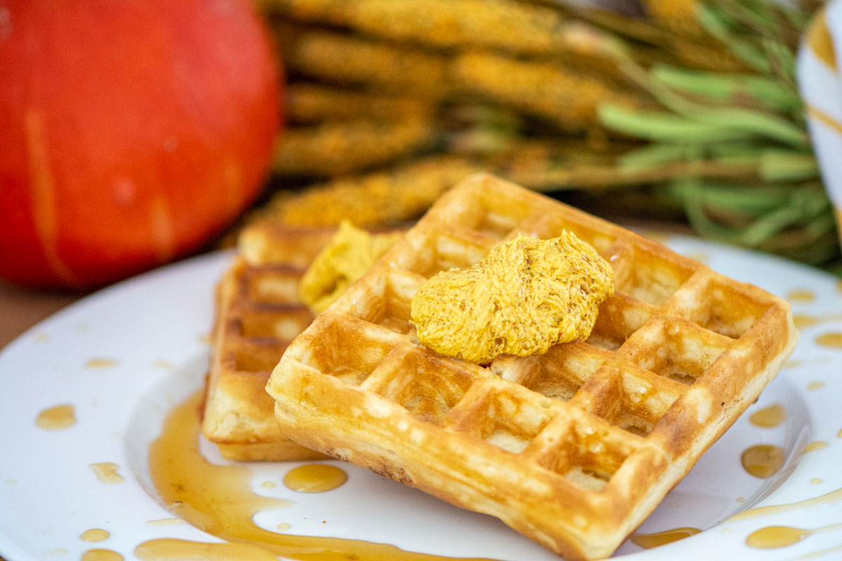 dollop of whipped pumpkin butter on a waffle with syrup