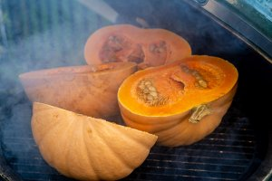 four pumpkin halves on the grill with light smoke billowing around them