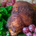 smoked turkey on a platter with parsley, grapes and an other fruit