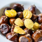 white bowl it peeled chestnuts and ones that have been scored and grilled