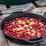 cast iron skilled on the grilling table filled with cranberries and other fruit.