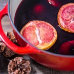 dutch oven with smoked grapefruit and oranges floating in the wine.