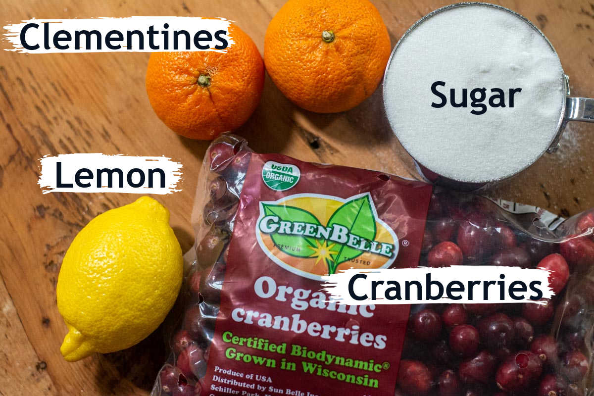 ingredient photo showing the cranberries, clementines, sugar and lemon.