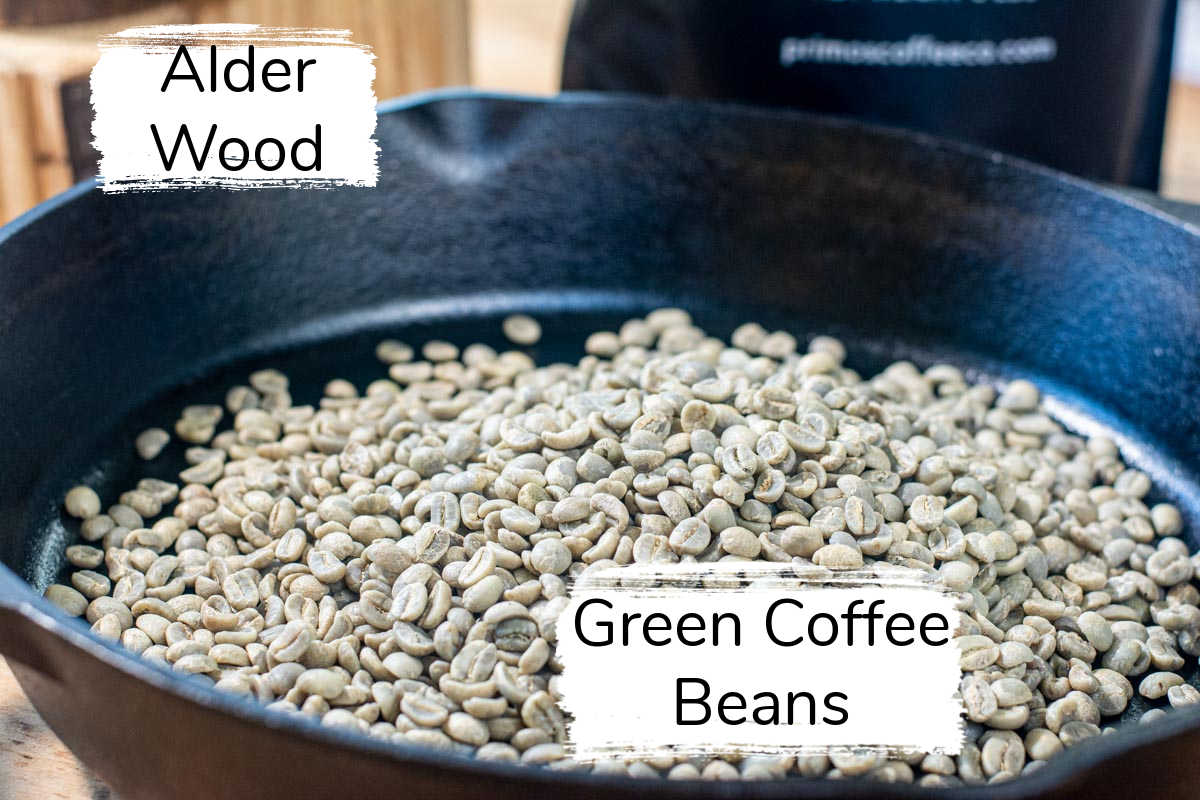 ingredient photo showing the green coffee beans in a cast iron skillet and alder in the background.