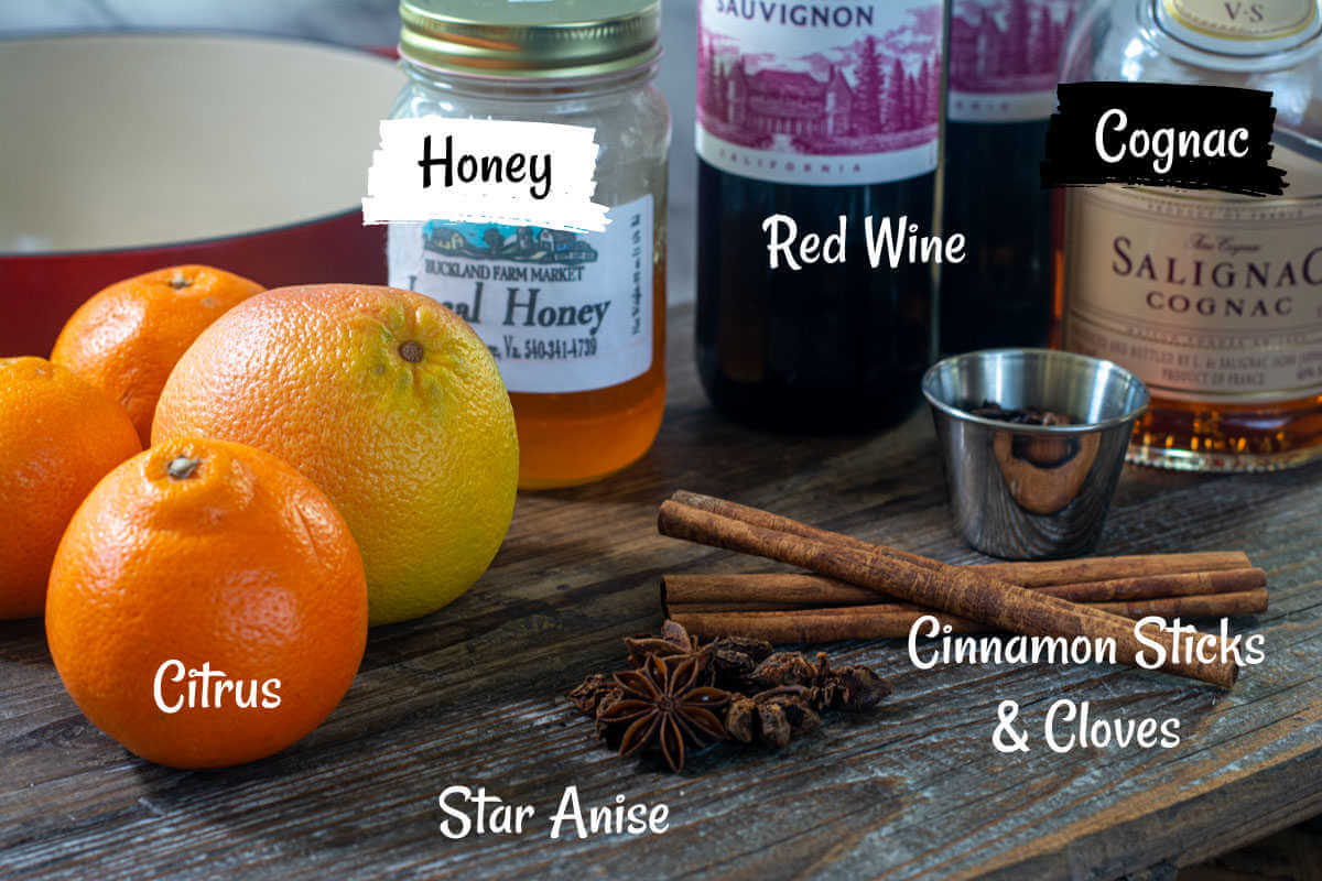 ingredients for the mulled wine on a cutting board. All of the ingredients have labels.
