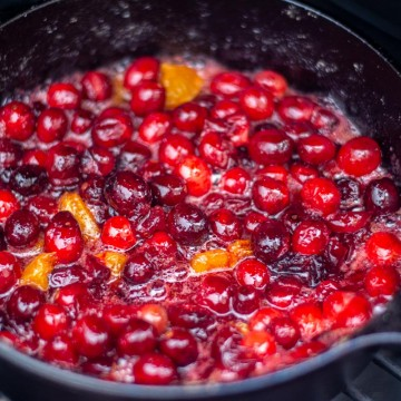 cranberries and clementines breaking down in the cast iron over the open flame of the grill.