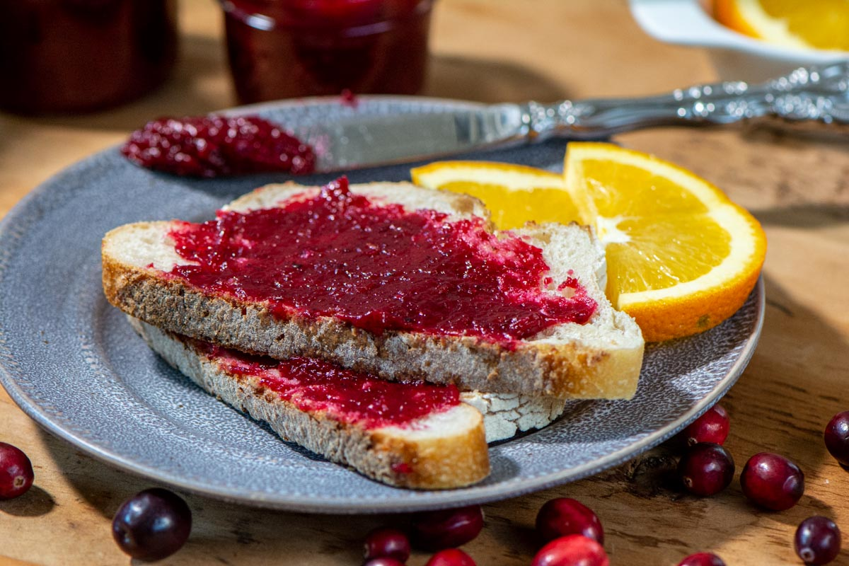 cranberry jam spread on toast with sliced oranges on a grey plate.