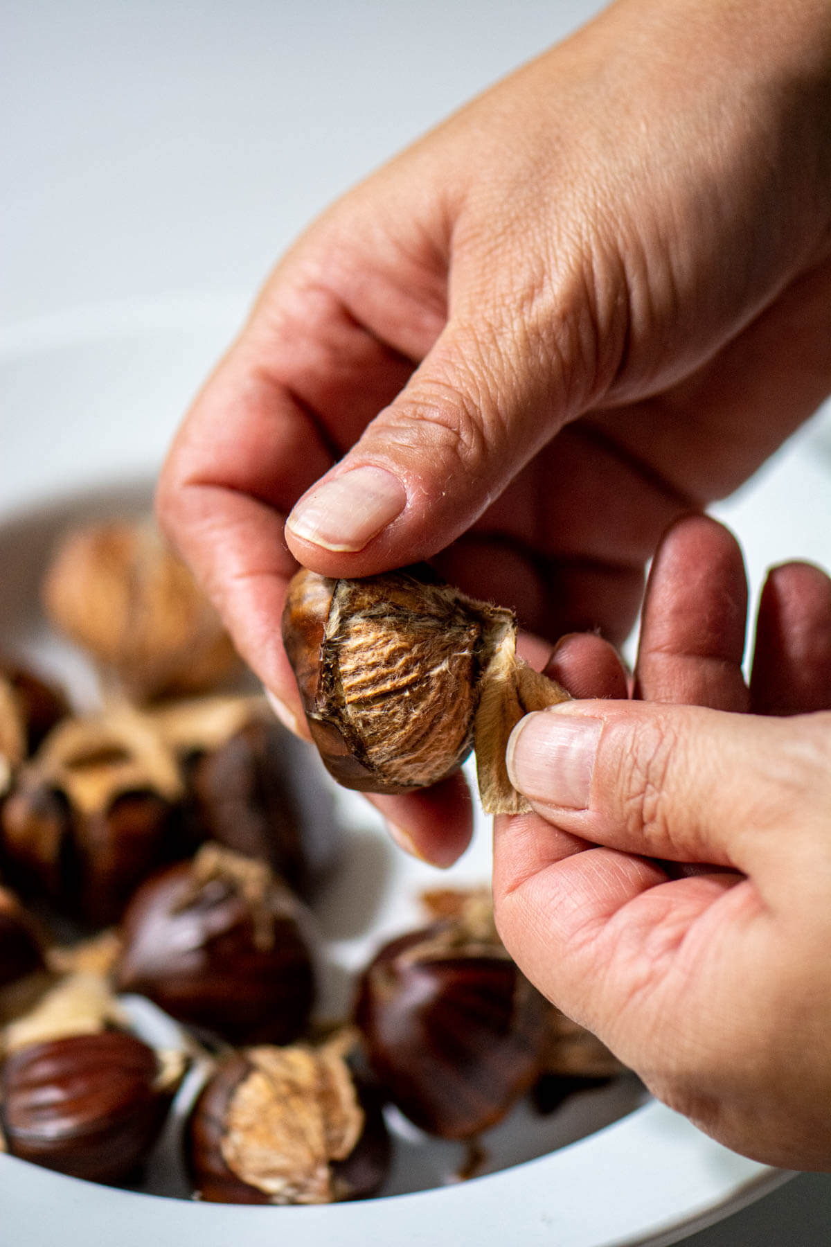 peeling chestnuts by hand when they are still warm