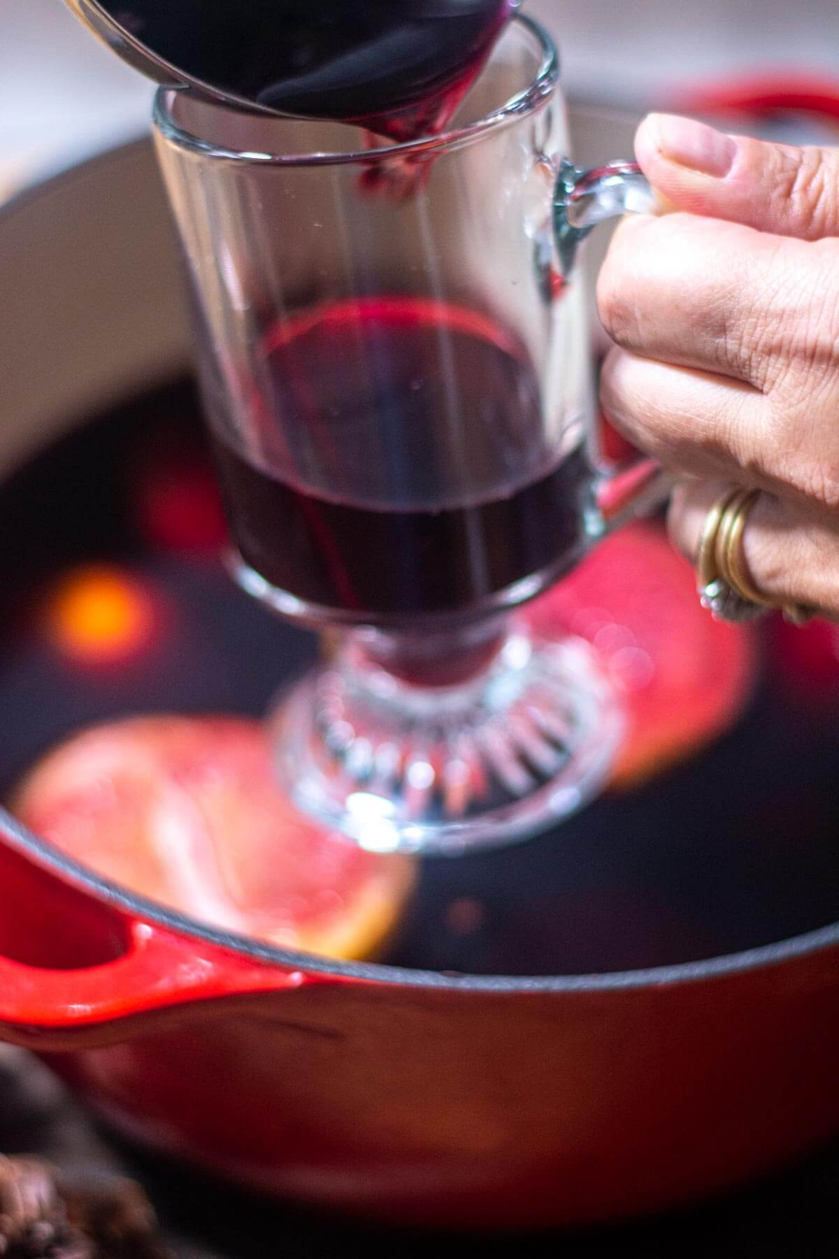 ladling the wine into a glass mug with the dutch oven in the bakground.