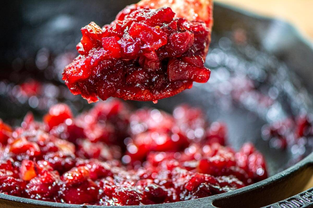Scooping up the thickened cranberry sauce from the skillet after it has cooled.