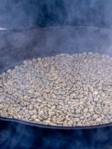 green coffee beans in a skillet on the grill with alder smoke.