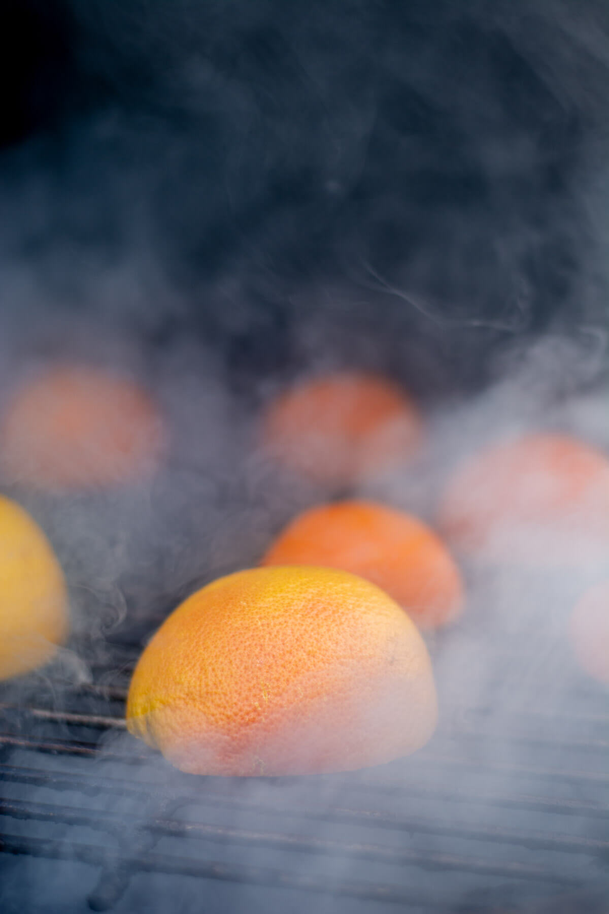 sliced grapefruit and oranges on the grill with smoke billowing.